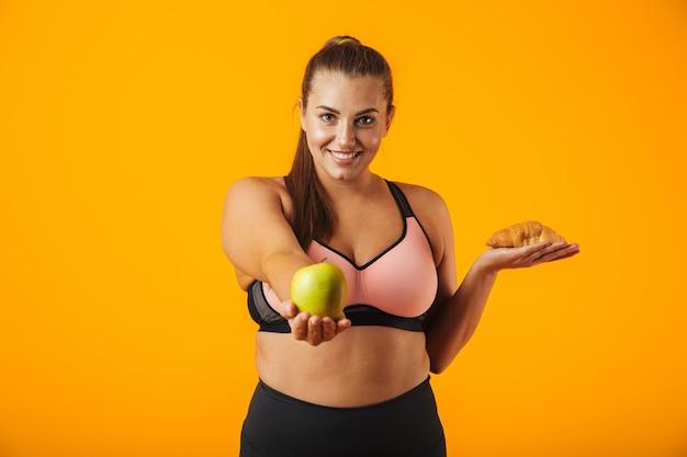 Wizerunek zdrowej kobiety pulchne w dresie, trzymając jabłko i rogalik w obu rękach, na białym tle nad żółtym tle