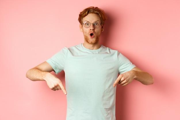Wizerunek zdumionego młodzieńca z rudymi włosami i brodą, noszącego okulary i koszulkę, wskazującego palcami w dół i wpatrującego się podekscytowany w kamerę, różowe tło.