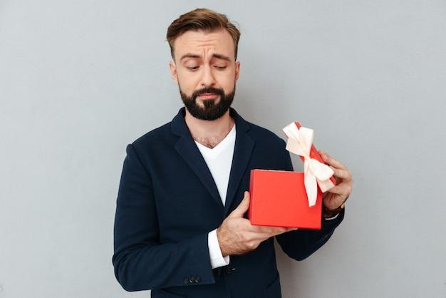 Wizerunek zdziwiony brodaty mężczyzna w biznesie odziewa otwarcie prezent