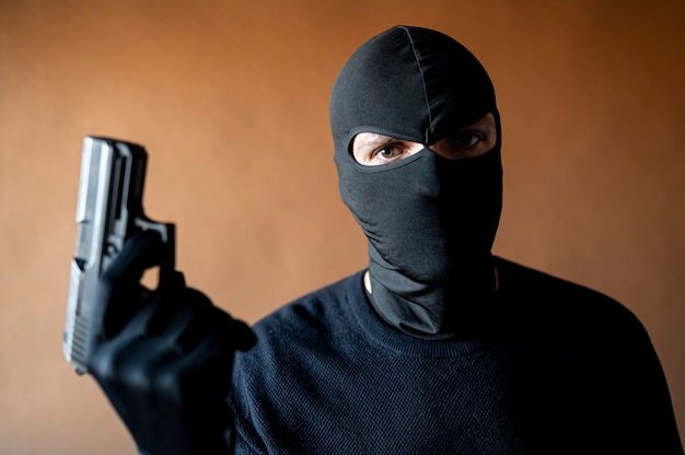 Wizerunek złodzieja z kominiarką i pistoletem w ręku