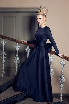 Wizerunek zmysłowej kobiety w czarnej sukience i akcesoriach z wieczorowym makijażem, pozuje na schodach
