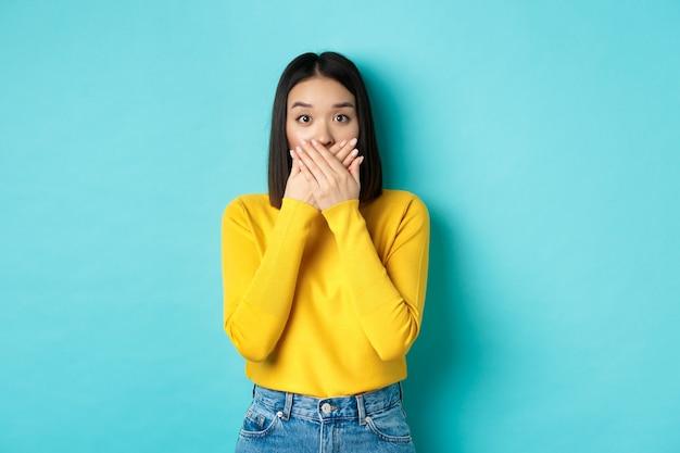 Wizerunek zszokowanej dziewczyny azjatyckiej zakrywającej usta i wpatrującej się w kamerę, ubrana w żółty sweter na niebieskim tle.