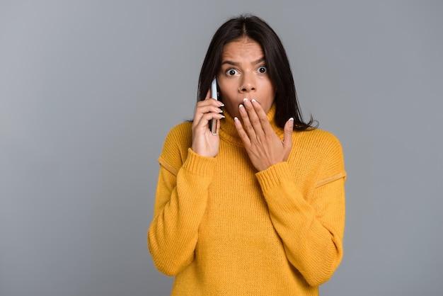 Wizerunek zszokowanej, zaskoczonej kobiety, pozowanie na białym tle na szarej ścianie, rozmawiając przez telefon komórkowy.