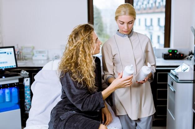 Wizyta kosmetyczki. wspaniała młoda kobieta trzyma butelkę kremu podczas rozmowy z jej kosmetologiem w klinice urody spa.