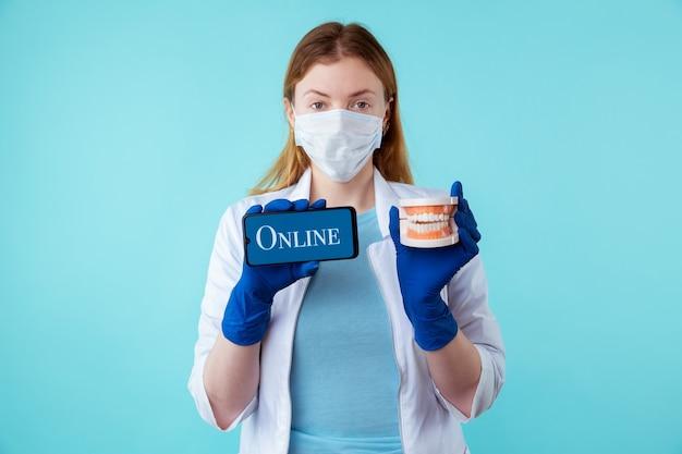 Wizyta u dentysty online z telefonu. kobieta lekarz posiadający instrumenty medyczne i telefon komórkowy na białym tle na niebieskim tle.