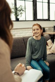 Wizyta u psychologa. radosna miła dziewczyna uśmiecha się siedząc na kanapie