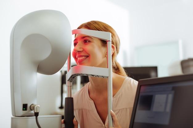 Wizyta w klinice okulistycznej. rudowłosa młoda atrakcyjna kobieta czuje się dobrze podczas wizyty w prywatnej klinice okulistycznej