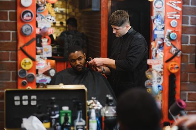 Wizyta w salonie fryzjerskim afroamerykanin w stylowym salonie fryzjerskim