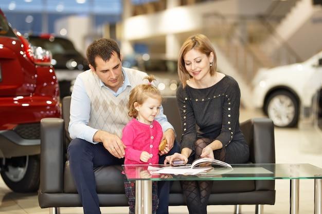 Wizyta w salonie. rodzina kupuje nowy samochód