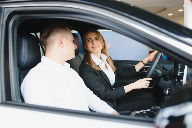 Wizyta w salonie samochodowym. piękna para patrzy na kamerę i uśmiecha się, siedząc w swoim nowym samochodzie