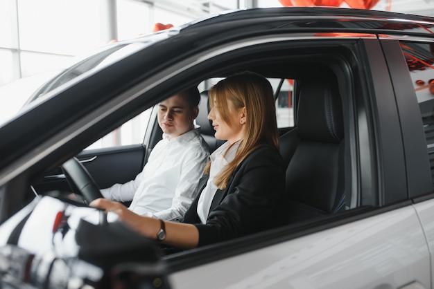 Wizyta w salonie samochodowym. piękna para patrzy na kamerę i uśmiecha się siedząc w swoim nowym samochodzie