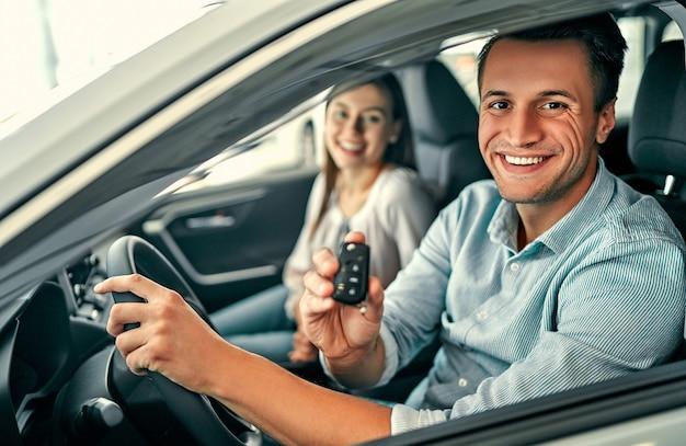 Wizyta w salonie samochodowym. piękna para trzyma kluczyk swojego nowego samochodu, patrzy w kamerę i uśmiecha się