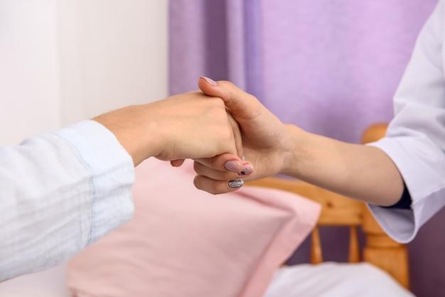 Wizyta w szpitalu. kobiece uściski dłoni pacjenta i lekarza z bliska