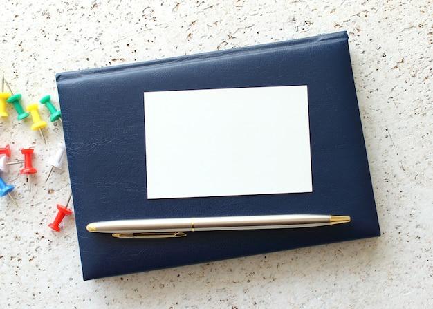 Wizytówka leżąca na niebieskim notebooku obok okularów. pomysł na biznes.