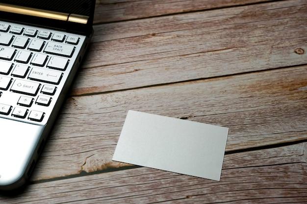 Wizytówka z laptopem na zalesionych białych wizytówkach na jasnym naturalnym drewnianym tle