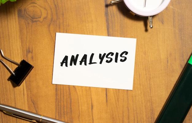 Wizytówka z napisem analiza leży na drewnianym biurku wśród artykułów biurowych. pomysł na biznes.