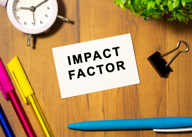 Wizytówka z napisem impact factor leży na drewnianym biurku wśród artykułów biurowych