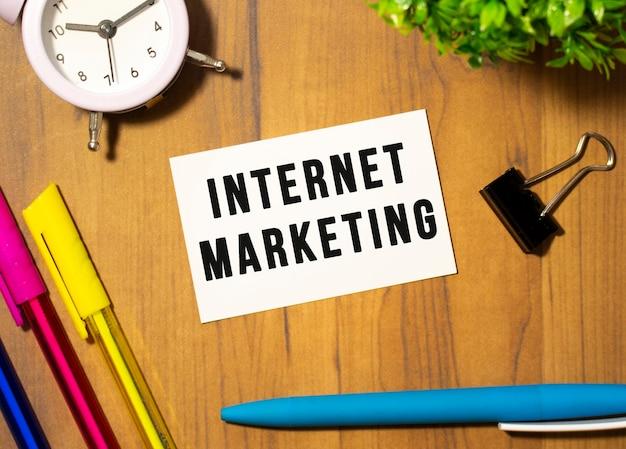 Wizytówka z napisem internet marketing leży na drewnianym biurku wśród artykułów biurowych. pomysł na biznes.