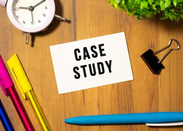 Wizytówka z tekstem case study leży na drewnianym biurku wśród artykułów biurowych