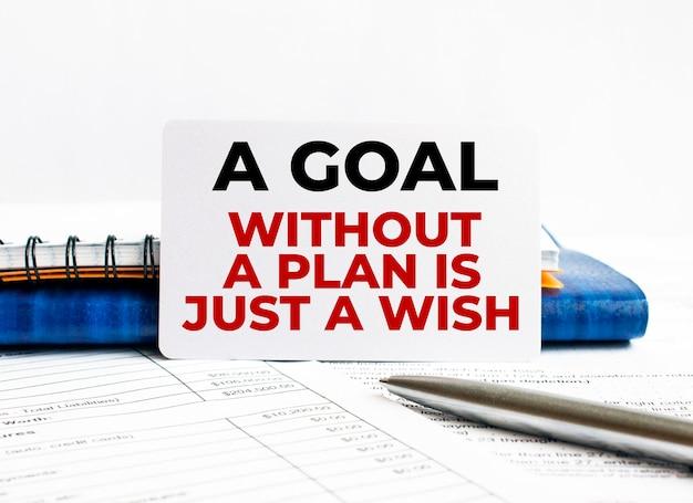 Wizytówka z tekstem cel bez planu to tylko życzenie leżące na niebieskim notesie.