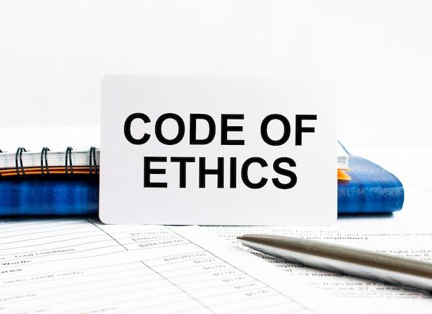 Wizytówka z tekstem kodeksu etyki leżącej na niebieskim notesie.