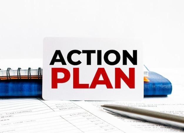 Wizytówka z tekstem plan działania leżący na niebieskim notebooku.