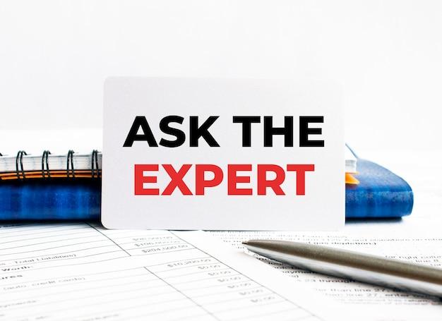 Wizytówka z tekstem zapytaj eksperta leżącego na niebieskim notesie