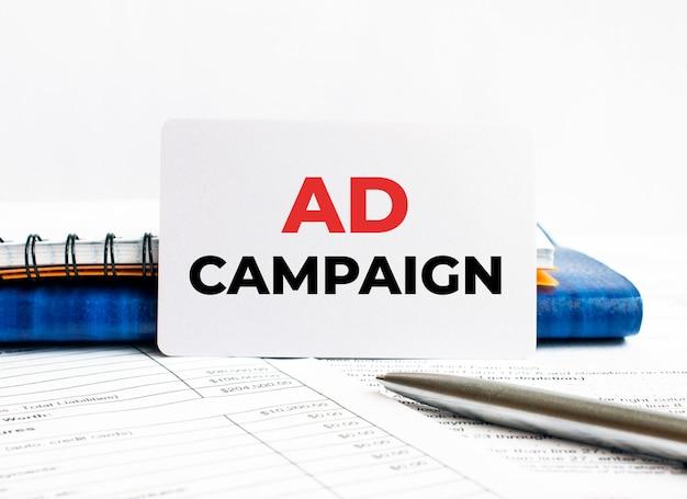 Wizytówka z tekstową kampanią reklamową leżącą na niebieskim notebooku, koncepcja