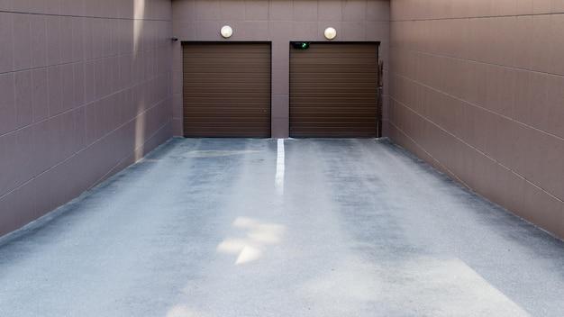 Wjazd na parking podziemny z zamykanymi bramami.