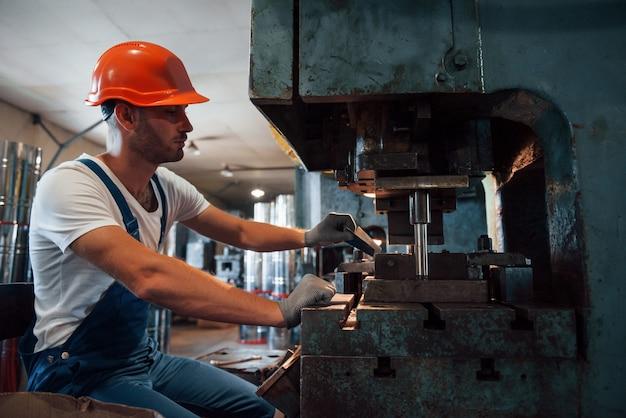 Wkłada blachę do maszyny. mężczyzna w mundurze pracuje nad produkcją. nowoczesna technologia przemysłowa.