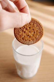 Wkładanie ciasteczek do mleka