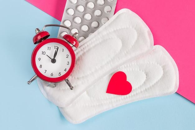 Wkładki menstruacyjne, budzik, hormonalne pigułki antykoncepcyjne. koncepcja okresu miesiączkowego. lek przeciwbólowy na ból menstruacyjny. koncepcja opóźnienia miesiączki