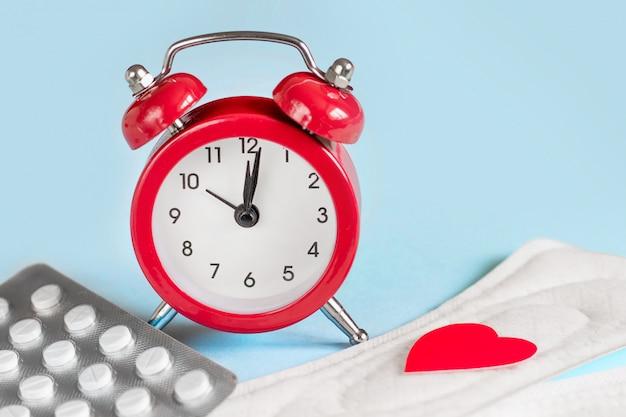 Wkładki menstruacyjne, budzik, hormonalne pigułki antykoncepcyjne. koncepcja okresu miesiączkowego. lek przeciwbólowy na ból menstruacyjny