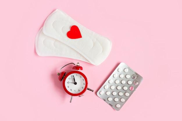 Wkładki menstruacyjne, budzik, hormonalne pigułki antykoncepcyjne. koncepcja okresu miesiączkowego.