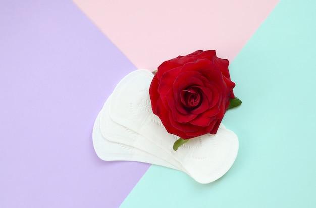 Wkładki menstruacyjne z czerwonym kwiatem róży leżą na wielokolorowym tle widok z góry