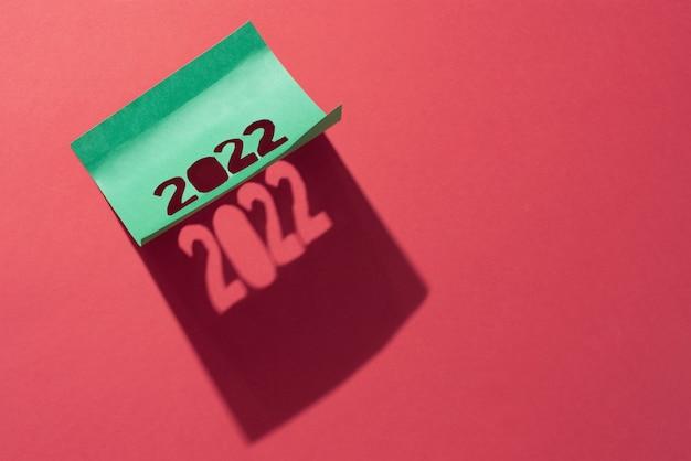 Wklejony papier firmowy z wyciętymi numerami 2022 i pięknym cieniem z niego na czerwonym tle, koncepcja noworoczna.