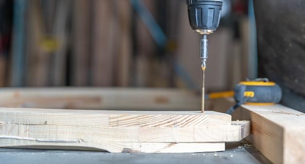 Wkręcanie drewnianych mebli w stolarce za pomocą wiertła elektrycznego