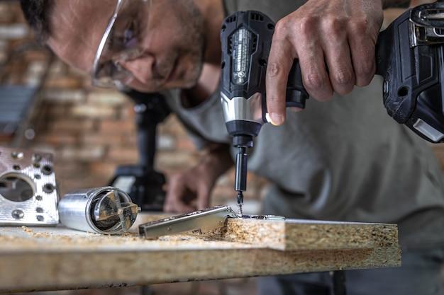 Wkręcanie wkrętu samogwintującego w metalowy otwór mocujący na listwie drewnianej za pomocą śrubokręta, praca stolarza.