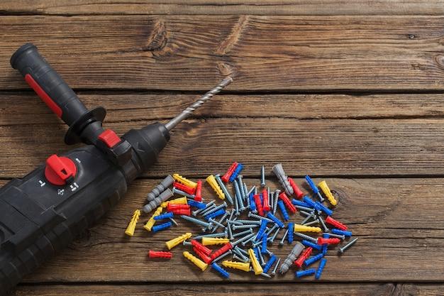 Wkrętak elektryczny i kołki na ciemnym drewnie