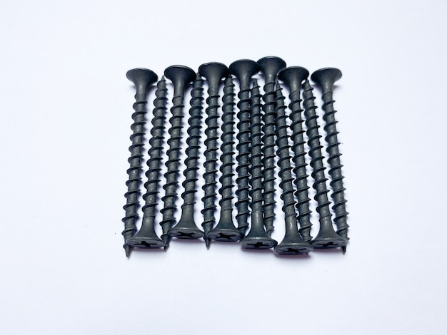 Wkręty samogwintujące na czarnym metalu na białym izolowanym tle