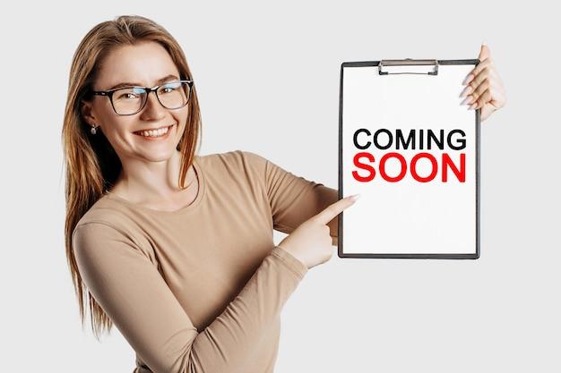 Wkrótce. piękna młoda biznesowa kobieta w okularach trzyma schowek z makiety miejsca na białym tle na szarym tle