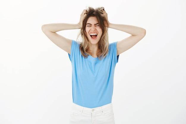 Wkurzona i wkurzona blond kobieta krzyczy, tracąc kontrolę nad emocjami