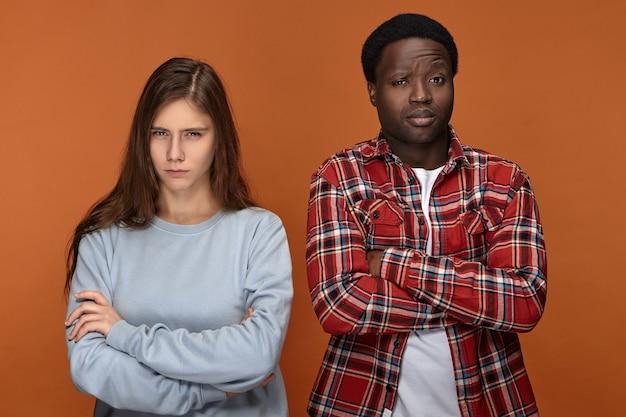 Wkurzony i poirytowany, młoda międzyrasowa para, żona i mąż, krzyżują ramiona i marszczą brwi, kłócąc się o remont domu. koncepcja problemów ludzi i relacji