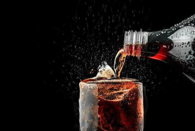 Wlać napój bezalkoholowy w szkło z odrobiną lodu na ciemnym tle.