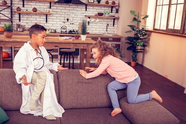 Włącz kreatywność. aktywna blondynka patrząca na kuzyna i bawiąca się razem