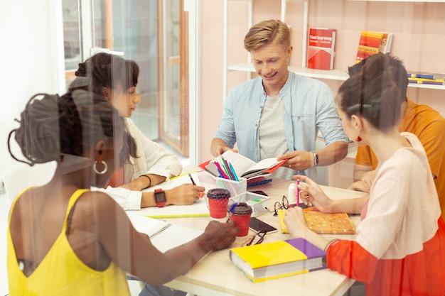 Włącz kreatywność. zadowolony mężczyzna otwierający książkę podczas przygotowań do egzaminu