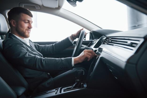 Włącz muzykę. nowoczesny biznesmen próbuje swojego nowego samochodu w salonie samochodowym
