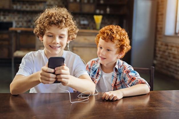 Włącz ten. urocze ujęcie dwóch dzieci w różnym wieku, siedzących obok siebie i skupiających swoją uwagę na ekranie smartfona, jednocześnie słuchając muzyki w domu.