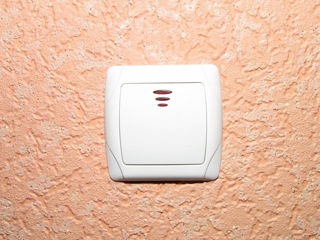 Włącz włącznik światła na ścianie pomarańczowej tapety