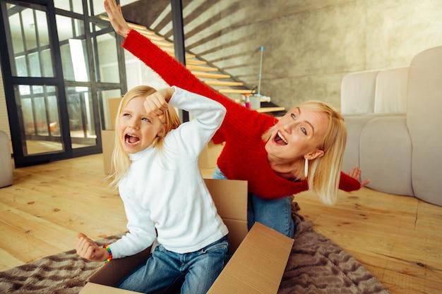 Włącz wyobraźnię. zadowolony dzieciak bawiący się z mamą, siedzący w pudełku